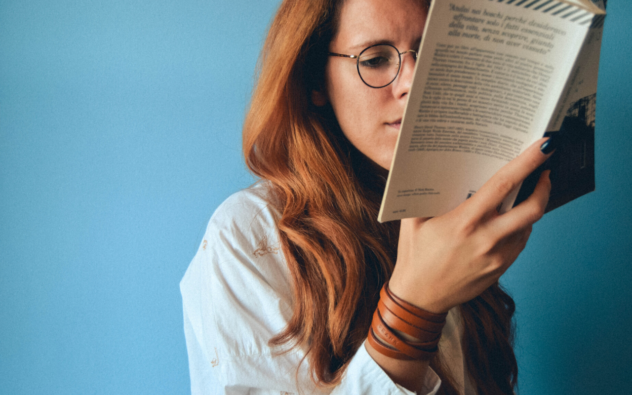 woman with glasses reading book